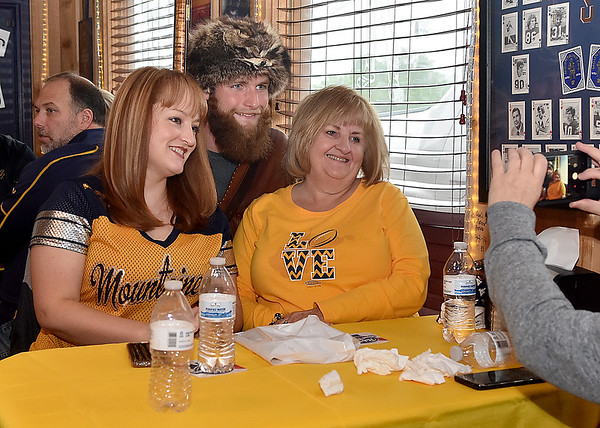(Brad Davis/The Register-Herald) Cool Ridge residents Heather Brooks, left, and Karen Brooks pose for a quick photo with Mountaineer Troy Clemons during the WVU Coaches' Caravan Thursday at Calacino's.