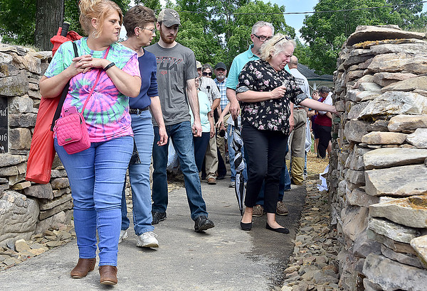 (Brad Davis/The Register-Herald) Residents take a walk through the newly dedicated Old Mill Park Flood Memorial Friday. At right, Lewisburg resident Andrea Morrison reacts as she comes across Dakota Stone's name on the Old Mill Park Memorial following its dedication Firday afternoon in White Sulphur Springs. Her husband Terry follows behind. Stone was a good friend of Andrea and Terry's son Max and they knew him well.