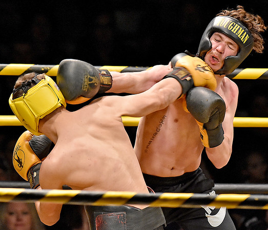 (Brad Davis/The Register-Herald) Beckley's Austin Showalter, right, catches a right from Sophia's Jhon Lilly in a light heavyweight matchup during the Original Toughman Contest Friday night at the Beckley-Raleigh County Convention Center. Showalter would win the fight.