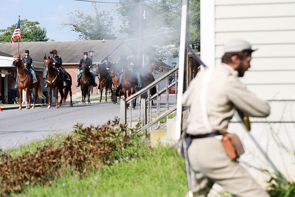 Civil War re-enactor Joseph Rose, from Pocahontas County, ducks behind a house after firing at the Federal Army cavalry during a battle between the local Home Guard and the Federal Army as part of Monroe County Heritage Day in Union on Saturday.  (Chris Jackson/The Register-Herald)