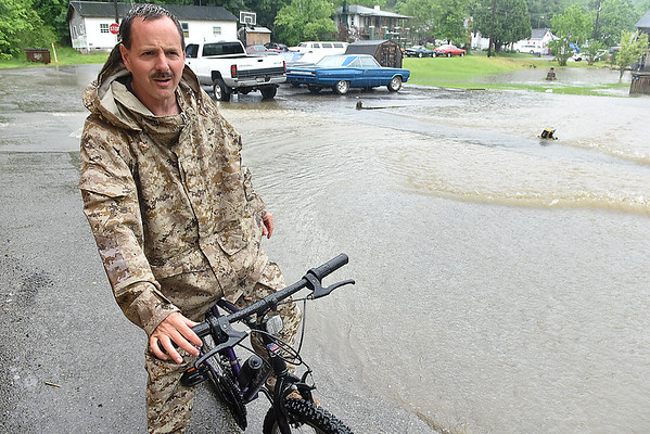 (Brad Davis/The Register-Herald) Scarbro Loop Road resident Jason McVey gets around the flooded areas of the neighborhood on a bike Monday afternoon.