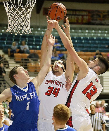 (Brad Davis/The Register-Herald) University's Ryan McCord, middle, and Geoff Hamperian, right, leap for a rebound with Ripley's Ty Johnson during Big Atlantic Classic action Friday afternoon at the Beckley-Raleigh County Convention Center.