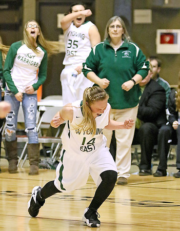 (Brad Davis/The Register-Herald) The Lady Warrior bench erupts in celebration with her as Wyoming East's Jazz Blankenship reacts to hitting a game tying three-pointer late in their game against St. Albans in the Big Atlantic Classic class AAA girls championship game Saturday night at the Beckley-Raleigh County Convention Center.
