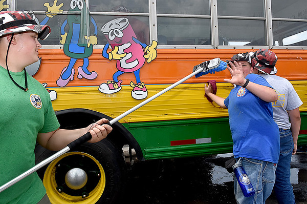 (Brad Davis/The Register-Herald) Illinois Scout Noah Reisetter, left, bugs his buddy Connor Rabey with a scrubber as they wash the recycling promotional bus at the Raleigh County Solid Waste Authority Thursday afternoon in Beckley.