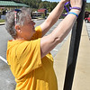 (Brad Davis/The Register-Herald) Women's Resource Center director of Public Relations and Fundraising, ties a purple ribbon to a tree around town for domestic violence awareness month Sunday afternoon in uptown Beckley. Bessie's Floral Designs in Oak Hill and Flowers by Nancy in Beckley donated the ribbons and materials to the Women's Resource Center.