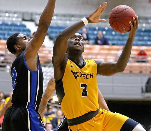(Brad Davis/The Register-Herald) WVU Tech's Junior Arrey drives and scores as Glenville State's Darhius Nunn defends during the team's first ever home game at the Beckley-Raleigh County Convention Center Wednesday night.
