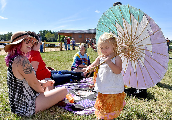 (Brad Davis/The Register-Herald) Mom Tori Lilly, left, has a laugh as her two-year-daughter Amehtyst Poland plays with an umbrella in the back yard area of Weathered Ground Brewery during their grand opening celebration Saturday afternoon in Cool Ridge.