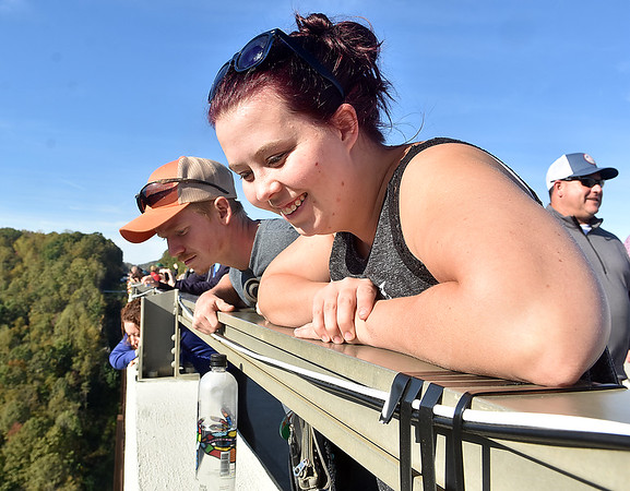 (Brad Davis/The Register-Herald) Elizabeth residents Abby and Zach Adams lean over the rail to watch the jumpers during Bridge Day Saturday afternoon.