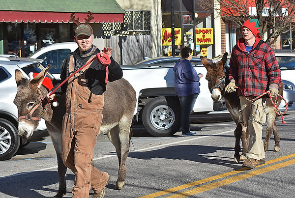 (Brad Davis/The Register-Herald) Austin McCoy, left, guides Cowboy while brother Ben guides Gingi, two Jerusalem donkeys, as they make their way along Main Street in Sophia during the town's annual Christmas Parade Saturday afternoon.
