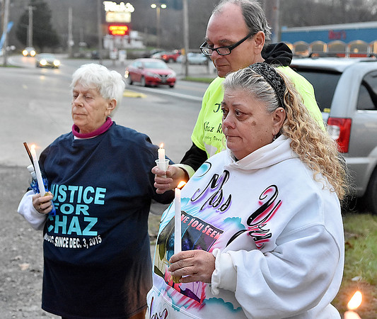 (Brad Davis/The Register-Herald) Mother Leisa Wellington, right, looks on during a candlelight vigil for son Chaz Richardson Wednesday evening in Glen Daniel next to the Whitesville State Bank. Chaz has been missing since December 2015 and would be 28 today. She is joined in the photo by Chaz's Grandmother Sandra Metheny, left, and family friend Dave Shannon.