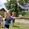 (Brad Davis/The Register-Herald) Five-year-old Hayleigh Scott chases a giant bubble during Saturday afternoon's Family Fair in White Sulphur Springs.