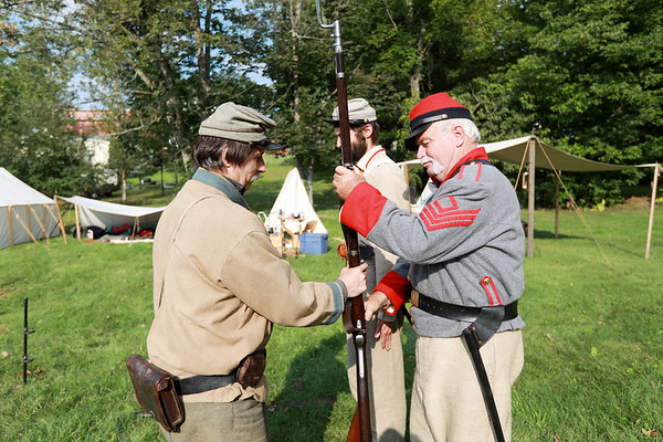 Civil War re-enactor Rick Henry, left, inspects Blaine Hypes, right, and Joseph Rose's rifles during an inspection prior to a skirmish between the local Home Guard and the Federal Army as part of Monroe County Heritage Day in Union on Saturday.  (Chris Jackson/The Register-Herald)