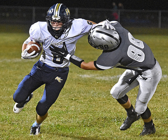 (Brad Davis/The Register-Herald) Nicholas County's Nick Kiser carries the ball as Westside defender Cody Justus tries to run him down Friday night in Clear Fork.