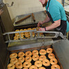 Jordan Southard flipping donuts so they are browned evenly on both sides at the Donut Connection.<br /> (Rick Barbero/The Register-Herald