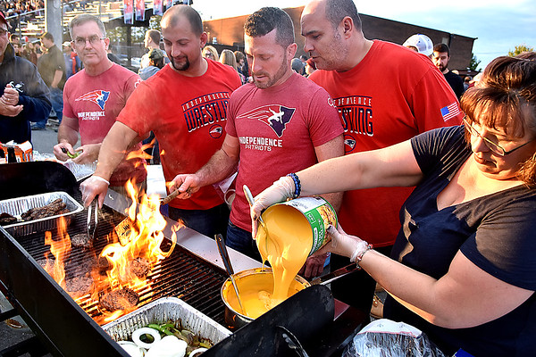 (Brad Davis/The Register-Herald) Independence grillin' crew members get the grub flowing prior to the Patriots' home game against visiting Shady Spring Friday night in Coal City. From right are Jodie Gilkerson (cheese), Kevin Adams (peeking over shoulder), Jeremy Hart (grillin), Jamie Bolen and Doug Moore (far left).