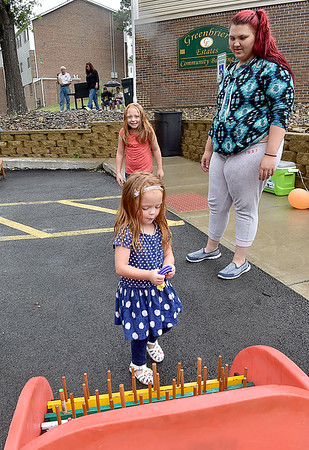 (Brad Davis/The Register-Herald) Resident Monica Todorovich, right, watches as sisters Makyria (nearest), 3, and Makensley Lester, 7, play a ring toss game during a community picnic at Greenbrier Estates Friday afternoon. Property manager Michelle Bennett, leasing agent Phil Spurlock and other facility officials threw a cook-out style gathering with games for kids and a visit from West Virginia Miners mascot Miner Mike.