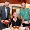 "(Brad Davis/The Register-Herald) United Bank's Chaz Turner, left, and YMCA of Southern West Virginia's Ryan Gilkerson, just two of the many local celebrities participating this year,  ""serve"" Women's Resource Center director Patricia Bailey as they pose for a Celebrity Night promo photo at Pasquale's Friday afternoon."