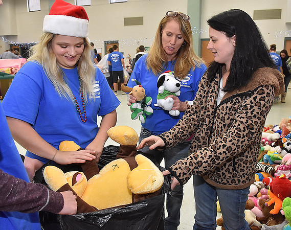 (Brad Davis/The Register-Herald) Kelly Byrd, right, is assisted by volunteers (from left) Cassidee Blankenship and Karen Haynes during the Wyoming County Toy Fund Sunday morning at Wyoming East High School.