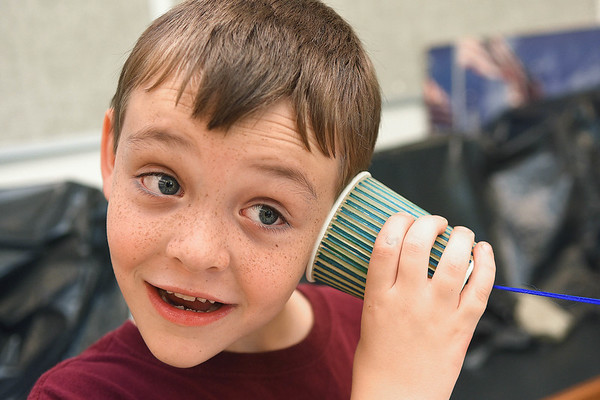 Colton Nutter, listening to another student talk through a cup phone during the Rainelle Elementary Energy Express program Tuesday Morning after first lady Cathy Justice read to students in the schools gym.<br /> (Rick Barbero/The Register-Herald)