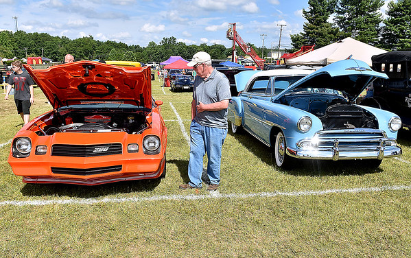 (Brad Davis/The Register-Herald) Princeton resident Randy Price checks out a couple of sweet rides during the Friends of Coal Auto Fair Saturday afternoon at the Raleigh County Memorial Airport.