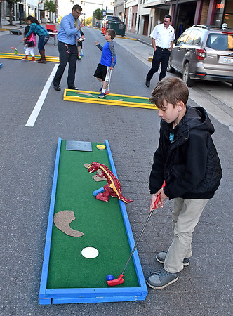 (Brad Davis/The Register-Herald) 10-year-old Nathan Hurt works his way through the mini golf course set up along Main Street in front of Foster's during Celebrity Night at Pasquale's Monday evening. Hurt would eventually be crowned the overall winner with the lowest score on the evening.