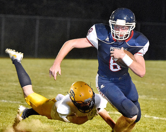 (Brad Davis/The Register-Herald) Independence's Adam Daniels avoids a tackle from Clay County defender Kenny Welch as he carries the ball Friday night in Coal City.