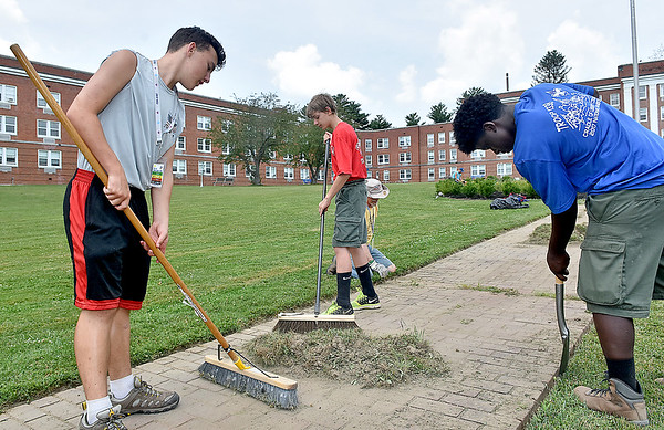 (Brad Davis/The Register-Herald) From left, Troop 1338 (Philadelphia, Pa.) Scouts Conor Murcar Trent Maines and Myron Davis sweep up pulled crab grass and weeds from sidewalks on the grounds of Jackie Withrow Hospital Thursday afternoon in Beckley.