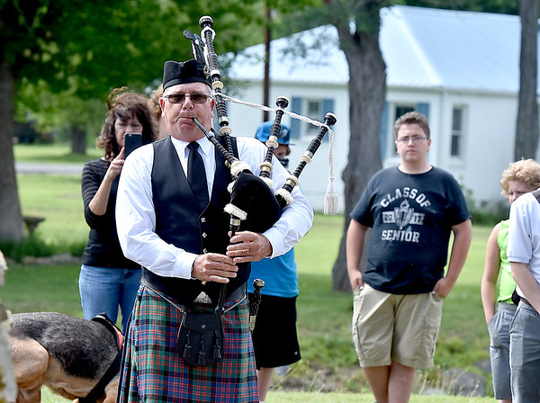 (Brad Davis/The Register-Herald) Bagpiper Don Dransfield plays Amazing Grace as he slowly marches through the newly dedicated Old Mill Park Flood Memorial, which bears the names of all White Sulphur Springs residents lost in last year's devasting floods.