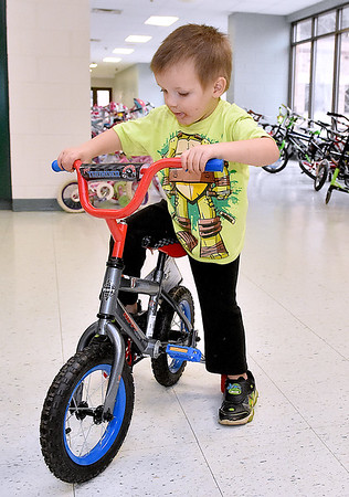 (Brad Davis/The Register-Herald) Three-year-old Christopher Neace hops on his brand new bike, courtesy of the Brothers of the Wheel Motorcycle Club's Southlands chapter, during the Wyoming County Toy Fund Sunday morning at Wyoming East High School.
