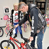(Brad Davis/The Register-Herald) Volunteer and Brothers of the Wheel M.C. member Archie Caldwell helps Joanna Vargas pick out the right sized bike for a family member receiving it during the Wyoming County Toy Fund Sunday morning at Wyoming East High School.