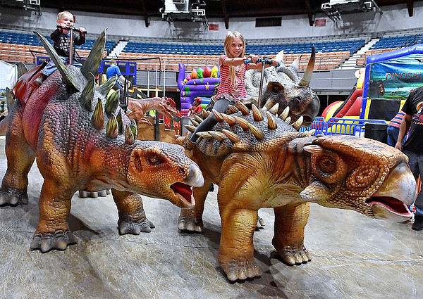 (Brad Davis/The Register-Herald) Nicholas County siblings Kamryn (right), 8, and little brother Preston Dorsey, 3, ride atop massive, life-like dinosaurs during a two-day weekend event called T-Rex Planet at the Beckley-Raleigh County Convention Center.