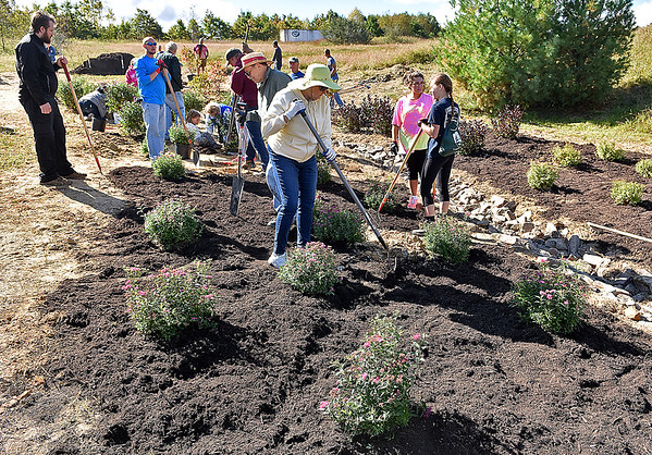 (Brad Davis/The Register-Herald) A small army of Piney Creek Watershed Association volunteers young and old work to construct a butterfly garden Saturday morning next to the YMCA Paul Cline Memorial Sports Complex.