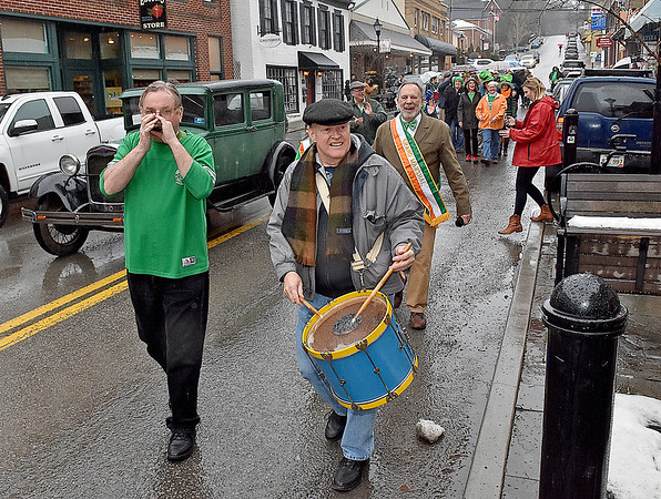 (Brad Davis/The Register-Herald) Patrons are all smiles despite the cold and rain as they make the grueling, 60-foot walk from The Wild Bean to Irish Pub in what's known far and wide as the shortest St. Patrick's Day Parade along Washington Street in Lewisburg Friday evening.