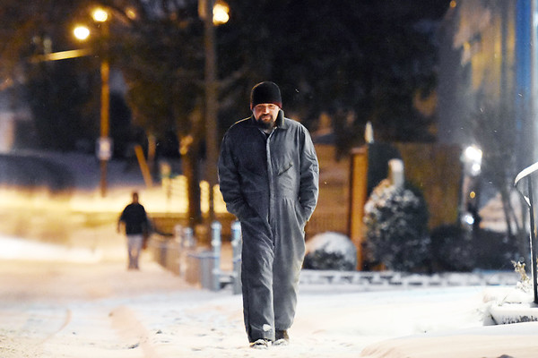 """Vince Farris, from Beckley, walks along Johnstown Rd. Tuesday as temperatures dip into the 20s in Beckley. """"I usually ride a motorcycle,"""" Farris said, """"but not in this. (Chris Jackson/The Register-Herald)"""