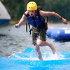 Scout Ryan Peene, 15, from Seattle, runs across a matt in the water at the obstacle course at Tridave Lake during the 2017 National Jamboree at The Summit Bechtel Reserve near Mt. Hope. (Chris Jackson/The Register-Herald)