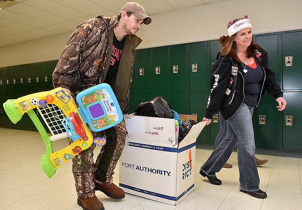 (Brad Davis/The Register-Herald) Volunteer and Brothers of the Wheel M.C. member Susie Canterbury helps Frank Lester haul his box full of goodies during the Wyoming County Toy Fund Sunday morning at Wyoming East High School.