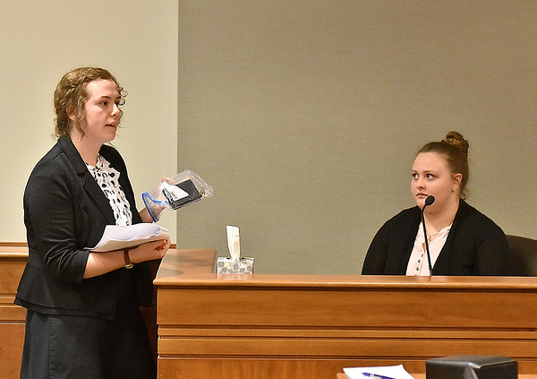 "(Brad Davis/The Register-Herald) ""Defense attorney"" Raven Livvy, left, holds evidence as she examines witness ""Officer Bates"" during a mock trial with middle and high school-aged homeschoolers from the Appalachian Christian Academy in Raleigh County Ciruit Court Monday afternoon."