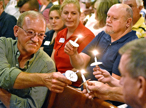 (Brad Davis/The Register-Herald) Residents help one another as the congregation lights their candles at the conclusion of Rainelle United Methodist's 2016 flood memorial service Friday night.