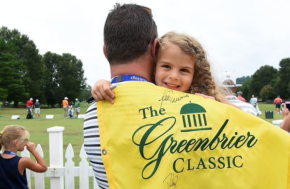 David Spence, of Fishersville, Va., holds his daughter, AddieGray Spence, watching golfers for The Greenbrier Classic practice on the driving range Tuesday morning.<br /> (Rick Barbero/The Register-Herald)