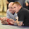 (Brad Davis/The Register-Herald) Liberty wrestling coach Nick Hylton, right, and official Guy Holliday watch the action and chat at mat level with Hylton's 7-month-old son Atticus Saturday afternoon at Shady Spring High School.