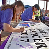 (Brad Davis/The Register-Herald) Eight-year cancer survivor Melinda Bennett, left, and her mother Shealvie Lilly, a 46-year survivor, each sign this year's commemorative banner during the American Cancer Society's Relay for Life atop Beckley's Intermodal Gateway Friday night.