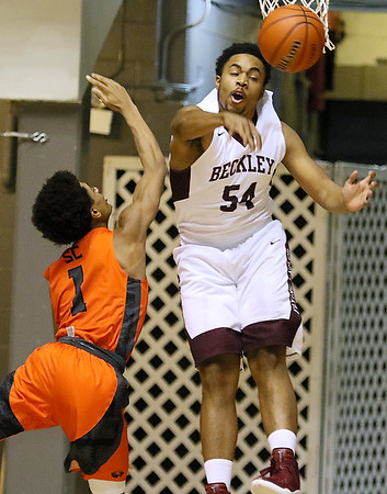 (Brad Davis/The Register-Herald) Woodrow Wilson's Brenton Walton unleashes a merciless block on South Charleston's James Moore as he tries to drive to the basket Wednesday night at the Beckley-Raleigh County Convention Center.