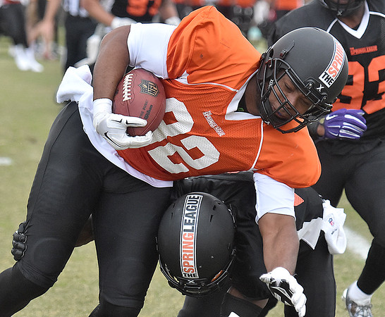 (Brad Davis/The Register-Herald) North (orange) tight end Chris Bazile is hit by South (black) defensive back LeQuan Lewis after making a catch during Spring League action Sunday afternoon in White Sulphur Springs.