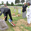 (Brad Davis/The Register-Herald) Oak Hill resident Margo Christian-Brooks, far right, looks on with friend Marla Snead as husband Bernardo sweeps debris from the headstone of her sister, the late Euretta Puryear (1929-1964) and her nephew Preston Puryear (1948-1966), who died tragically in a car accident in Beckwith just two years after Euretta passed due to brain cancer in 1964. The Christians have four generations of family buried in   and spent Sunday afternoon cleaning up their grave sites and placing flowers on them.