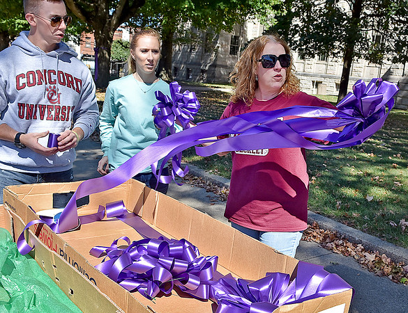 (Brad Davis/The Register-Herald) Women's Resource Center volunteer and Concord University professor Lori Pace, right, distributes large, purple ribbons to fellow volunteers Christian Harvey and Brooke Cole as they hang them around town for domestic violence awareness month Sunday afternoon in uptown Beckley. Bessie's Floral Designs in Oak Hill and Flowers by Nancy in Beckley donated the ribbons and materials to the Women's Resource Center.