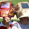 Nate Lesher, 8, and Aidan Lesher, of Anstaed, view the solar esclipes with welder masks at Grnadview State Park Monday afternoon.<br /> (Rick Barbero/The Register-Herald)