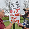 (Brad Davis/The Register-Herald) Woodrow Wilson athletic director Tim Carrico installs a sign asking that folks don't feed the ducks and geese with help from property maintenance worker Brandon Sgro around the pond in front of the school Wednesday afternoon.