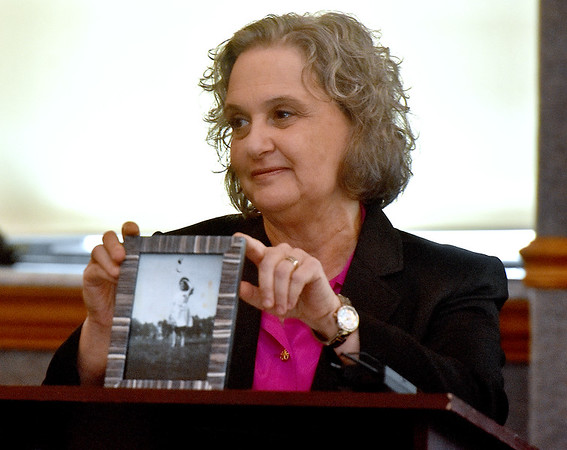 (Brad Davis/The Register-Herald) Simone Lotven Sofian, Ph.D., holds up an enlarged photo of her late mother taken when she was a teenager in the early 1940's prior to speaking about the plight of Jews in France during the Holocaust Sunday afternoon inside WVU Tech's Carter Hall. What's difficult to see in the photo is a yellow star of David on her dress and the scene of the photo, a public park that was forbidden to Jews during that time period. Her mother would later join the French resistance and survive the war.