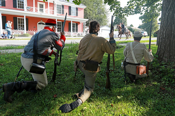 Civil War re-enactors posing as the Home Guard watch as a calvary commander for the Federal Army rides by during a battle between the local Home Guard and the Federal Army as part of Monroe County Heritage Day in Union on Saturday.  (Chris Jackson/The Register-Herald)