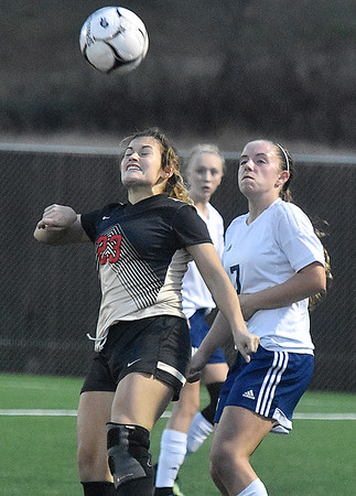 (Brad Davis/The Register-Herald) University's Keely Hinkle heads the ball as it's sent downfield before Hedgesville's Hunter Taylor can get there during Class AAA Girls State Soccer Tournament action Friday night the YMCA Paul Cline Memorial Sports Complex.